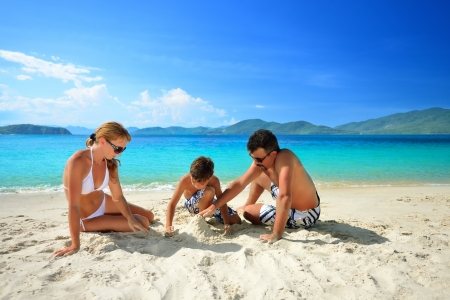 Happy family relaxing on the beach on a background of the islands