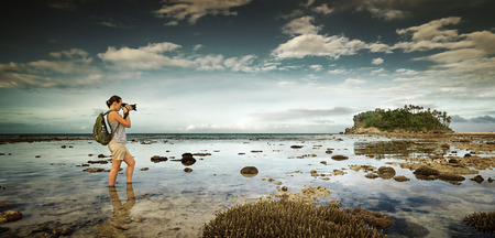 standing in the water traveler woman with backpack taking a landscape of nearby amazing island. Traveling along Asia, active lifestyle concept