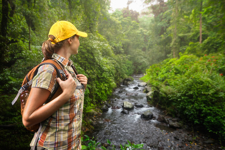 Foto de Young woman hiker with backpack standing and enjoying rain forest and river view. Lombok, Indonesia. Tourist hiking in the deep jungle - Imagen libre de derechos