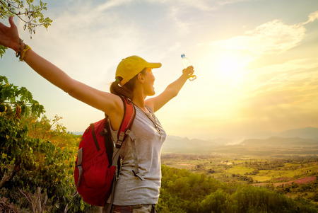 Foto de Portrait of happy traveler with backpack and a bottle of water standing on top of the mountain and enjoying valley view with raised hands. Mountains landscape, travel to Asia, happiness emotion, summer holiday concept - Imagen libre de derechos