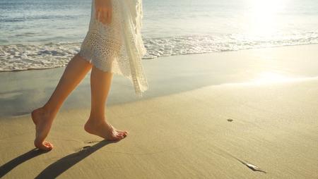 Foto de Young girl in white dress walking alone on the sandy beach at sunrise.Closeup detail of female feet and golden sand on beach. - Imagen libre de derechos