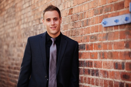 Professional man leaning against a brick wall outdoors