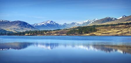 Scottish Highlands Landscape. Mountain range reflections on a lake in Scotland ona  sunny day.