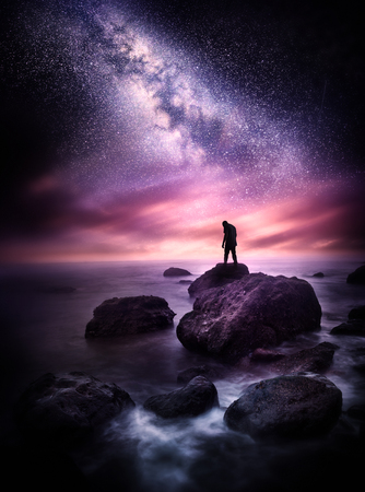 Night time Sea landscape with the Milky Way. A man stands on a rocky shore line with the stars above him. Photo composite.