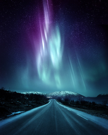 Photo for A quite road in Norway with a spectacular Northern Light Aurora display lighting up the night sky above the mountains. A popular destination within the arctic circle for hunting the Northern Lights. Photo Composite. - Royalty Free Image