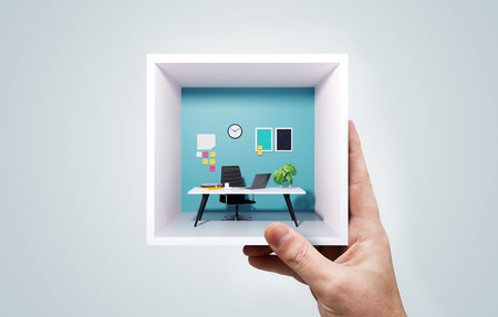 Photo pour A businessman holding up a miniature square office in his hand. Portable co-working work space business concept. Mixed media image. - image libre de droit