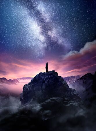 Foto de Night sky long exposure landscape. A man standing on a high rock watching the stars rise into the night sky. Photo composite. - Imagen libre de derechos