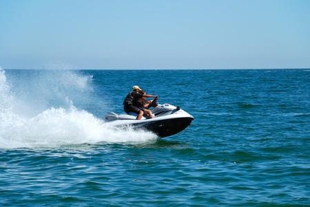 Photo pour Man on a high speed jet ski with water spray - image libre de droit