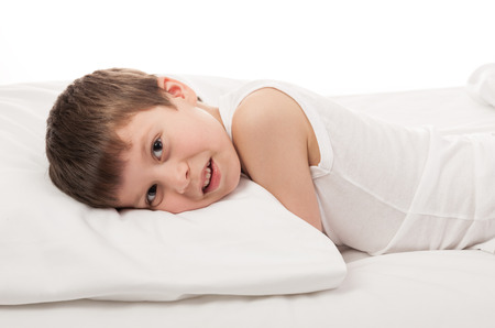 boy lying in bed on white