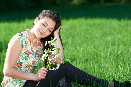 beautiful girl sitting on a glade in the woods, bright sun and shadows on the grass