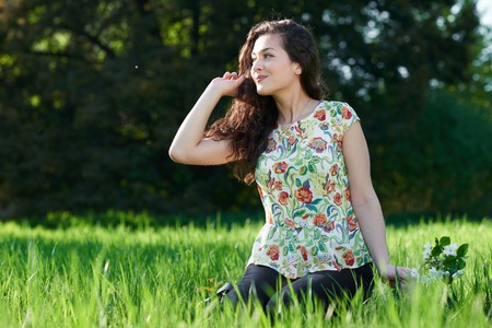 beautiful girl sitting on a glade in the park, bright sun and shadows on the grass