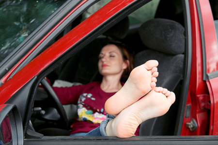 young woman driver resting in a red car, put her feet on the car window, happy travel concept