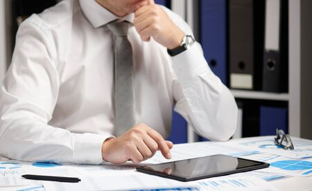 Photo pour Businessman working with tablet pc, calculating, reading and writing reports. Office employee, table closeup. Business financial accounting concept. - image libre de droit