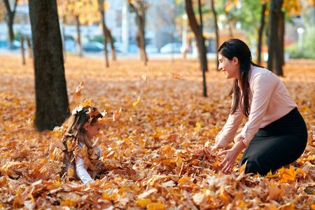 Photo pour Happy family having holiday in autumn city park. Children and parents posing, smiling, playing and having fun. Bright yellow trees and leaves - image libre de droit