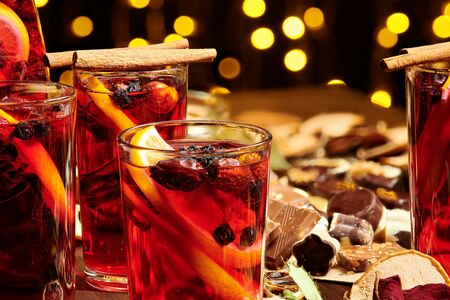 Photo pour Christmas mulled wine or gluhwein with spices, chocolate sweets and orange slices on rustic table, traditional drink on winter holiday, christmas lights and decorations - image libre de droit