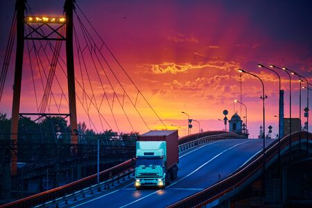 truck with container rides over the bridge, beautiful sunset, freight cars in industrial seaport, the road goes up