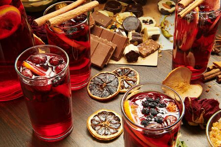 Photo pour Christmas mulled wine or gluhwein with spices, chocolate candies, sweets and orange slices on rustic table, traditional drink on winter holiday, christmas lights and decorations - image libre de droit