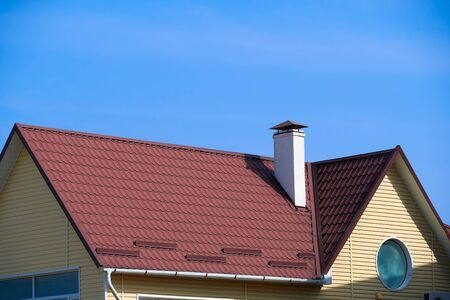 Photo pour roof and chimney of small house - red profile roofing sheets steel, yellow siding wall and blue sky - image libre de droit