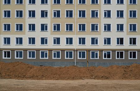 construction process and development of house area, land grading or earthwork, facade of a new multi-storey building