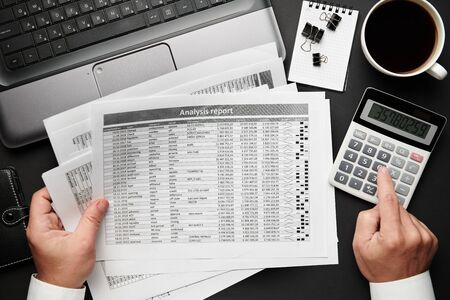 Photo for Top view of businessman's hands working with financial reports. Modern black office desk with laptop, notebook, pencil and a lot of things. Flat lay table layout. - Royalty Free Image