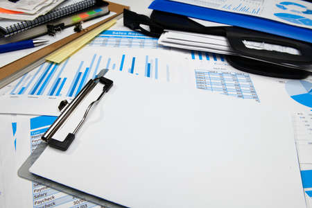 Foto de business office desk closeup - financial reports, analysis and accounting, set of documents, tables and graphs, various items for bookkeeping, calculator - Imagen libre de derechos