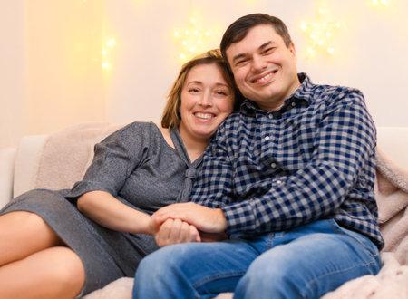 Foto de portrait of adult romantic couple sitting on a couch at home, holiday lights on a wall - Imagen libre de derechos