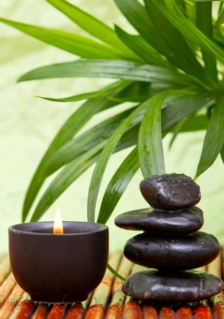 Balanced pebbles with aromatherapy candle and bamboo leaves