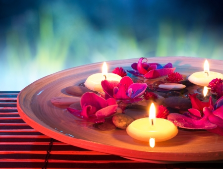 Photo pour dish spa with floating candles, orchid, in garden  - image libre de droit