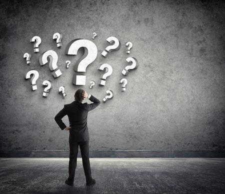 Photo pour Thoughtful businessman with questions marks - image libre de droit