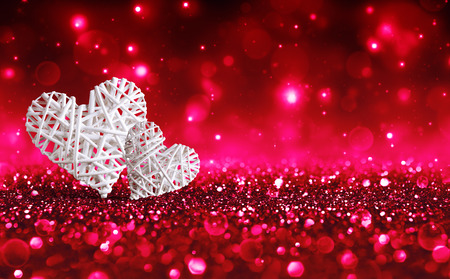 Foto de Two Wicker Hearts On Red Sparkle Glitter - Imagen libre de derechos