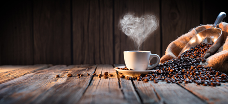 Photo pour Traditional Coffee Cup With Heart-Shaped Steam On Rustic Wood - image libre de droit