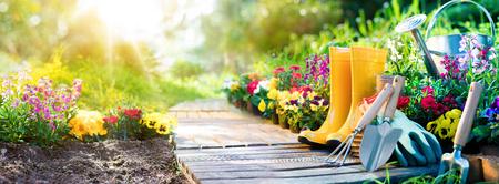 Foto de Gardening - Set Of Tools For Gardener And Flowerpots In Sunny Garden - Imagen libre de derechos