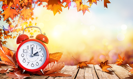 Foto de Daylight Savings Time Concept - Clock And Leaves On Wooden Table - Imagen libre de derechos