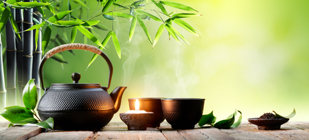 Photo for Black Iron Asian Teapot and Cups With Green Tea Leaves - Royalty Free Image