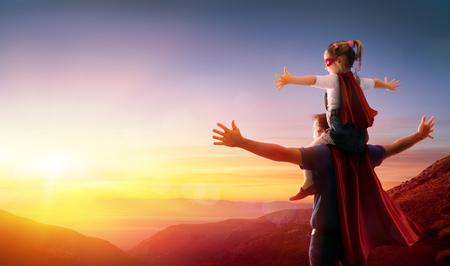 Foto de Daughter And Her Father Dressed As Heroes Watching The Sunset - Imagen libre de derechos