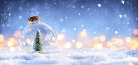 Foto de Snow Ball With Christmas Tree In It And Lights On Winter Background - Imagen libre de derechos