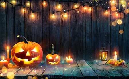 Foto de Halloween - Jack O 'Lanterns - Candles and String Lights On Wooden Table - Imagen libre de derechos