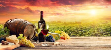 Photo for Barrel Wineglasses Cheese And Bottle In Vineyard At Sunset - Royalty Free Image