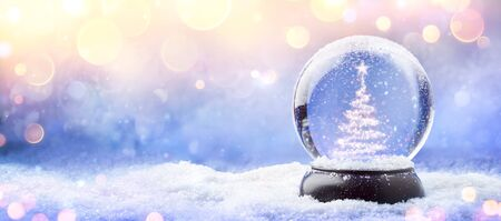 Foto de Shiny Christmas Tree In Snow Globe On Snow With Golden Lights - Imagen libre de derechos