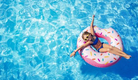 Photo pour Funny Child On Inflatable Donut In Pool - image libre de droit
