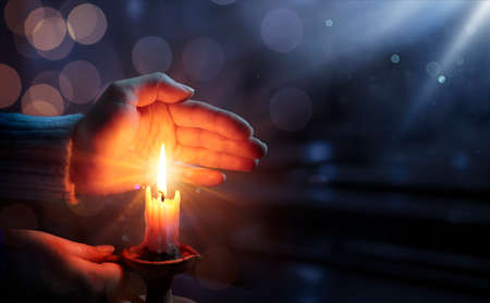 Photo for Defocused Hope Concept - Hands Holding Candle With Shining Flame And Blurry Lights - Royalty Free Image