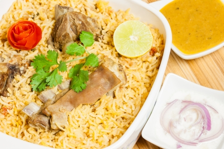 Closeup view from the top of delicious mutton  lamb  biryani garnished with tomato peel, cilantro and lemon  It is served with onion salad  raita  and vegetable curry