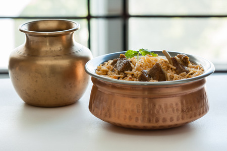 Mutton biryani - Closeup view of delicious mutton lamb biryani with mint garnish and served in authentic copper bowl. Natural light used.