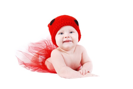 Adorable baby girl in red tutu and ladybug hat lying on white background