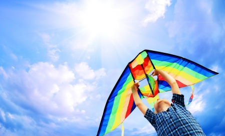 Photo for Happy little boy flies a kite in the sunny sky - Royalty Free Image