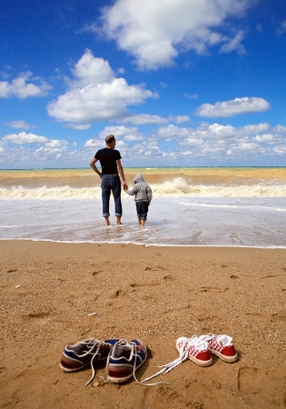 Father with son walk on the sea beach at the storm day