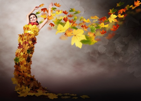Beautiful girl in dress from autumn leaves on  abstract windy background