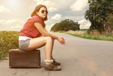 Photo pour Young girl on the empty highway waiting for free car - image libre de droit