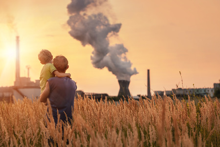 Ecological concept image  Father with son looking on chemical plant emissions at sunset time