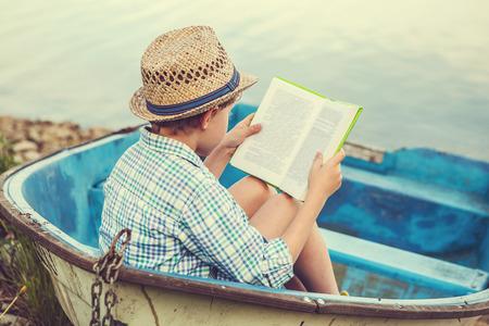 Photo pour Reading boy in old boat - image libre de droit